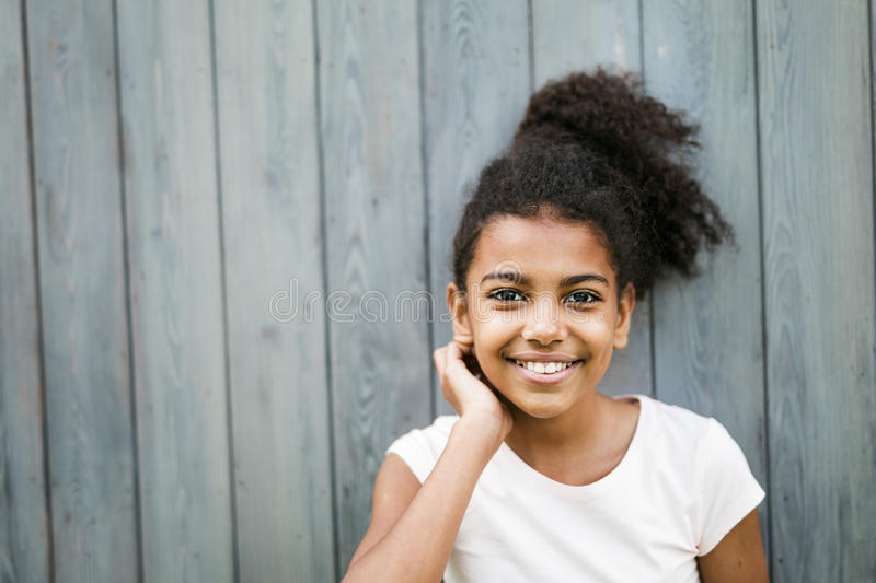 Portrait of a smiling girl standing at wall royalty free stock photo