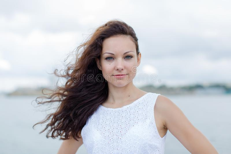 Portrait of girl with a barely noticeable smile. Portrait of smiling girl. Girl in white sleeveless dress looks at camera with a barely noticeable smile royalty free stock photos