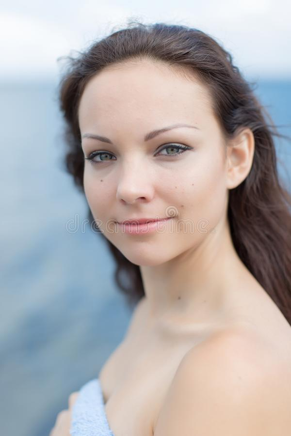 Wrapped in a towel girl with a barely noticeable smile. Portrait of smiling girl. Wrapped in a towel the girl looking at camera with a barely noticeable smile stock image