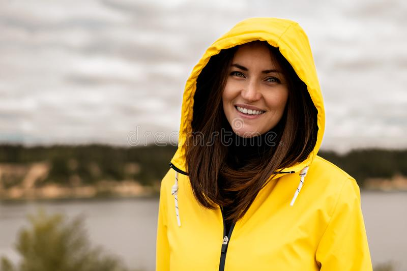 Portrait of smiling girl with yellow hooded raincoat on lake background with copy space royalty free stock photo