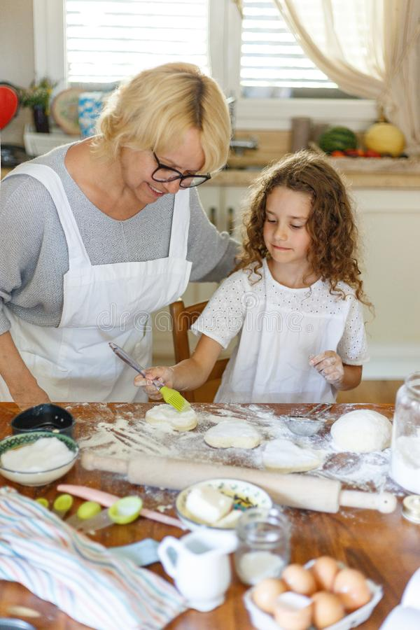 Portrait of a smiling granddaughter and grandmother cooking together. In kitchen. Family in kitchen. Vertical view. stock photography