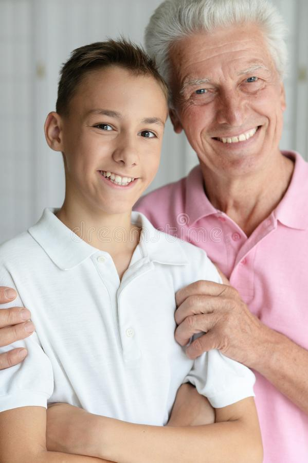 Smiling grandfather and grandson. Portrait of smiling grandfather and his teen grandson stock image