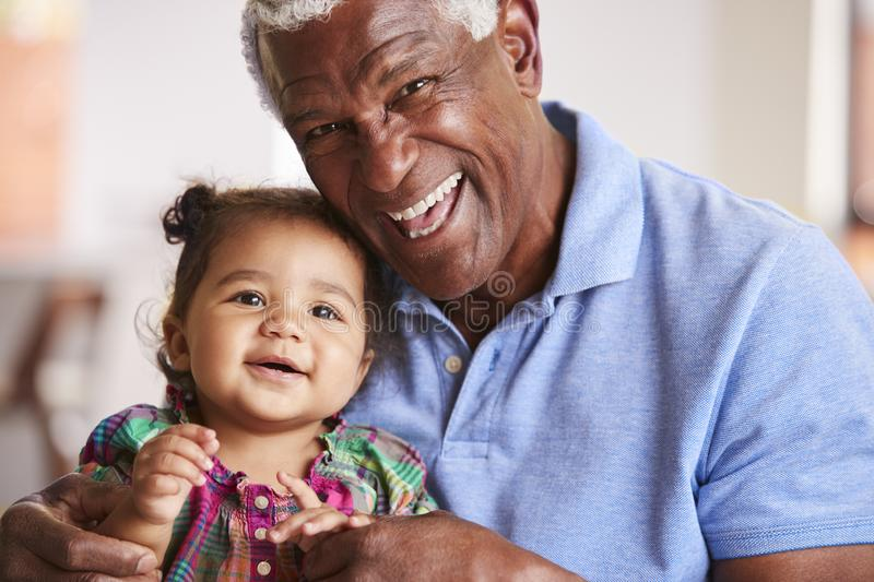 Portrait Of Smiling Grandfather Sitting On Sofa At Home With Baby Granddaughter stock photos