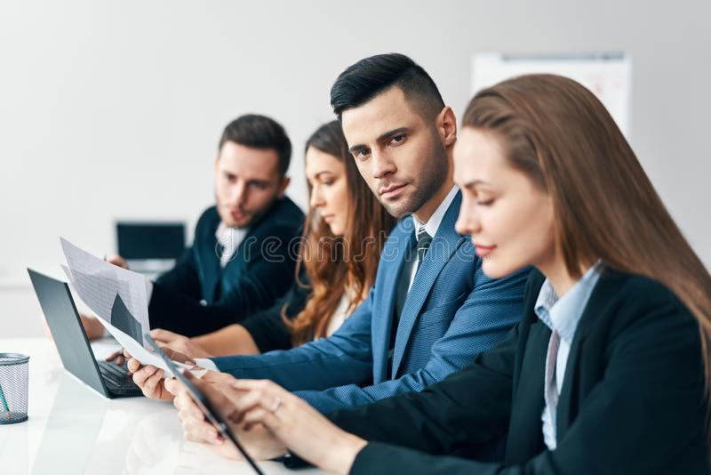Portrait of smiling group of business people sitting in a row together at table in a modern office stock photo
