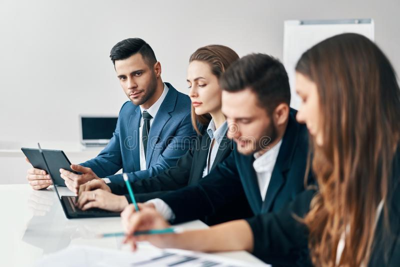 Portrait of smiling group of business people sitting in a row together at table in a modern office royalty free stock image