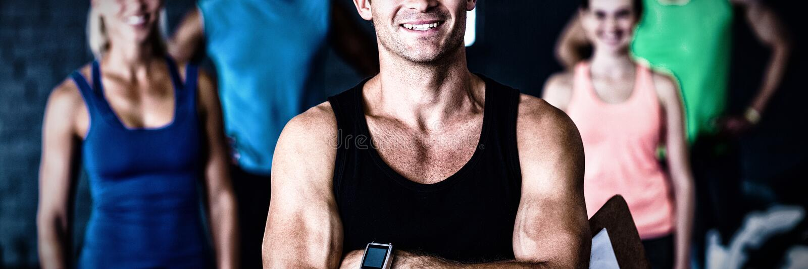 Portrait of smiling gym trainer holding clipboard royalty free stock images