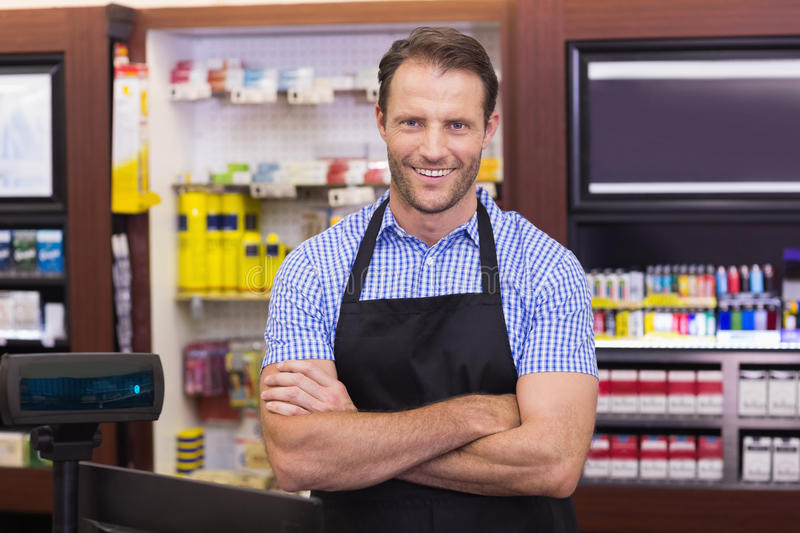 Portrait of a smiling handsome with arms crossed. In supermarket royalty free stock photography
