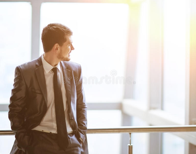 Portrait of a smiling handsome businessman on a window background looking to the side of a virtual text stock images