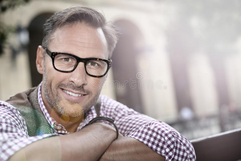 Portrait of smiling handsome man hanging outdoors stock photography