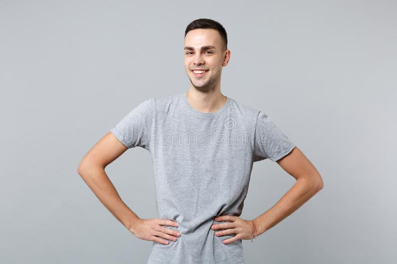 Portrait of smiling handsome young man in casual clothes standing with arms akimbo on waist isolated on grey wall royalty free stock photography