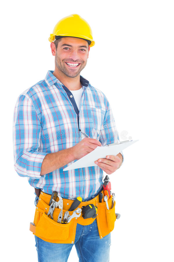 Portrait of smiling handyman writing on clipboard royalty free stock photo