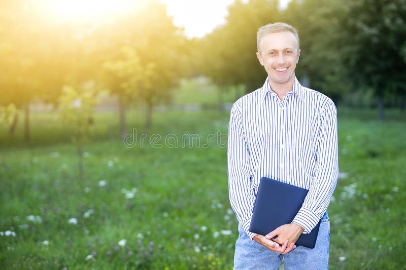 Portrait of Smiling Happy Caucasian Man In Casual Clothing Posing with Laptop Outdoors on Nature Background royalty free stock image
