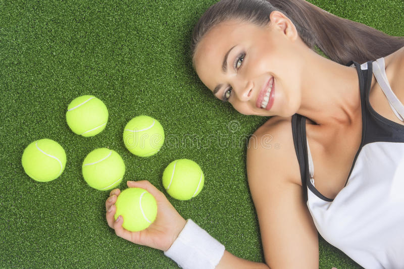 Portrait of Smiling and Happy Female Sportswoman Lying on Artificial Grass Surface With Tennis Balls stock photo