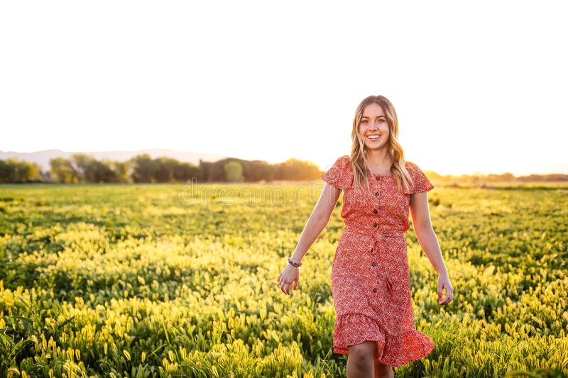 Portrait of a Happy girl walking among the wild flowers on a summer evening stock images