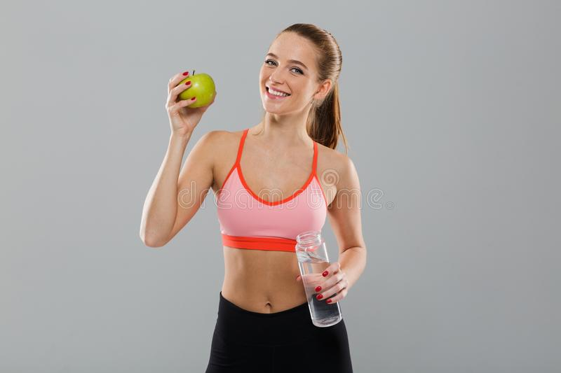 Portrait of smiling healthy sports girl holding green apple royalty free stock photo