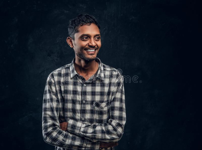 Portrait of a smiling Indian guy wearing a checkered shirt posing with his arms crossed and looking sideways stock images