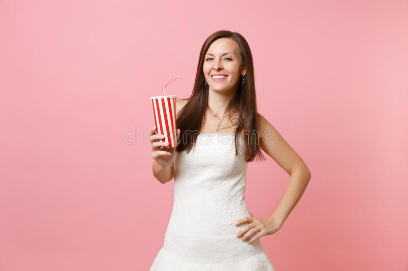 Portrait of smiling joyful bride woman in beautiful white wedding dress standing and holding plastic cup with cola or stock photo
