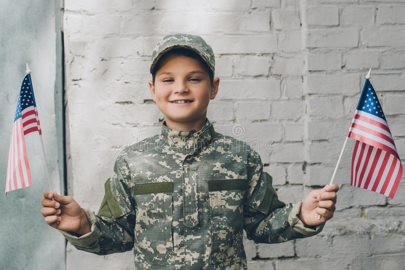 portrait of smiling kid in camouflage clothing holding american flagpoles with grey brick wall royalty free stock photo