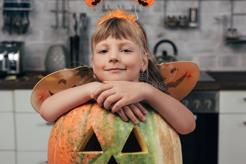 portrait of smiling kid in halloween costume leaning on big carved pumpkin stock photo