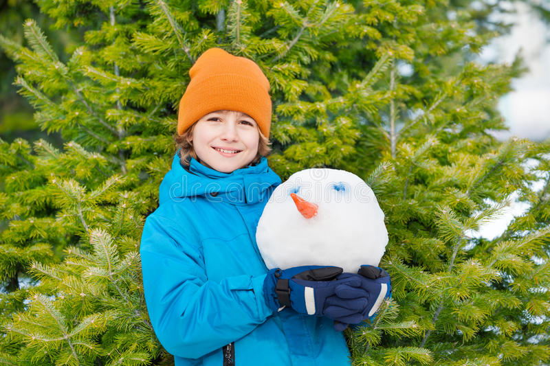Portrait of smiling kid holding snowman's head royalty free stock photo