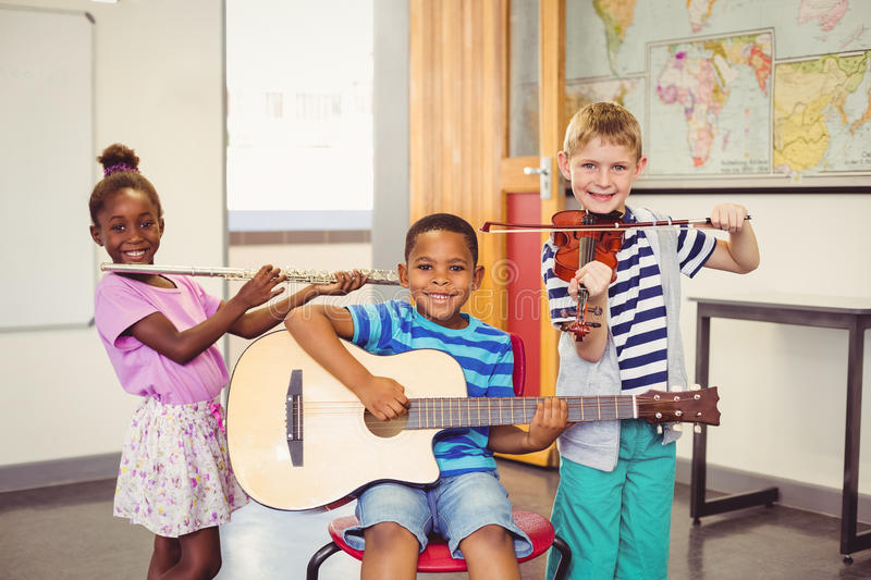 Portrait of smiling kids playing guitar, violin, flute in classroom stock photography