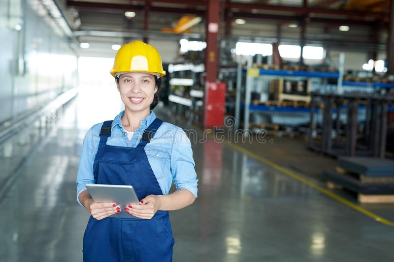 Female Engineer at Factory. Portrait of smiling Latin-American woman wearing hardhat smiling cheerfully looking at camera while enjoying work in modern factory royalty free stock photo