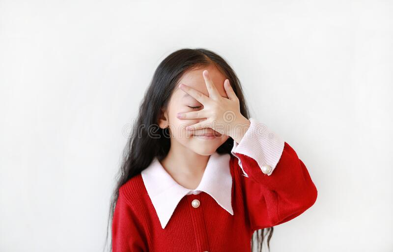 Portrait of smiling little Asian child girl in scarlet red dress covering eyes with hand isolated over white background stock images