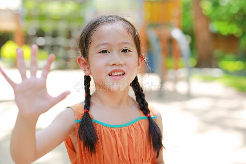 Portrait of smiling little Asian child girl showing palm or high five fingers for stop sign in the garden outdoor. Focus on kid royalty free stock image