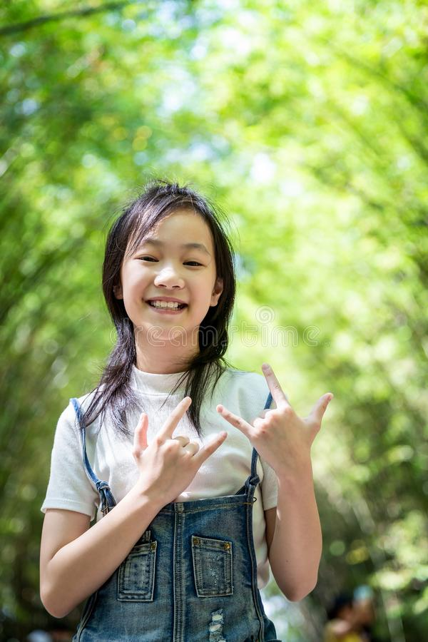 Portrait of smiling little asian girl right sign language meaning I Love You and look at the camera on bamboo forest,green nature stock photography