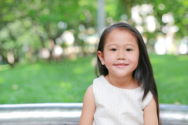 Portrait of smiling little Asian kid girl in nature park with looking camera royalty free stock image