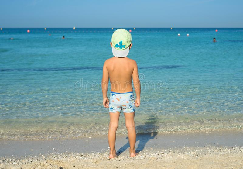 Portrait smiling little baby boy playing in the sea, ocean. Positive human emotions, feelings, joy. Funny cute child making vacati. Ons and enjoying summer stock image