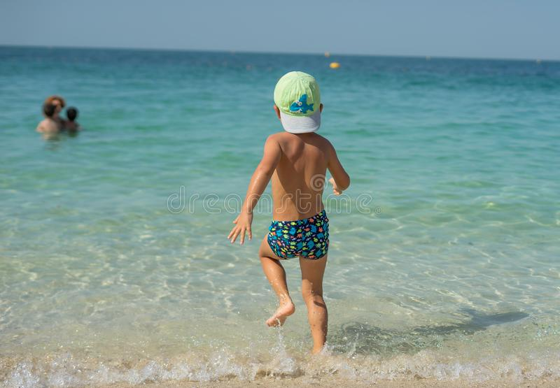 Portrait smiling little baby boy playing in the sea, ocean. Positive human emotions, feelings, joy. Funny cute child making vacati. Ons and enjoying summer royalty free stock photography