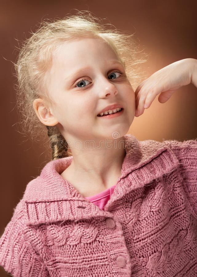 Portrait of smiling little blond girl`s waist on the root background stock image
