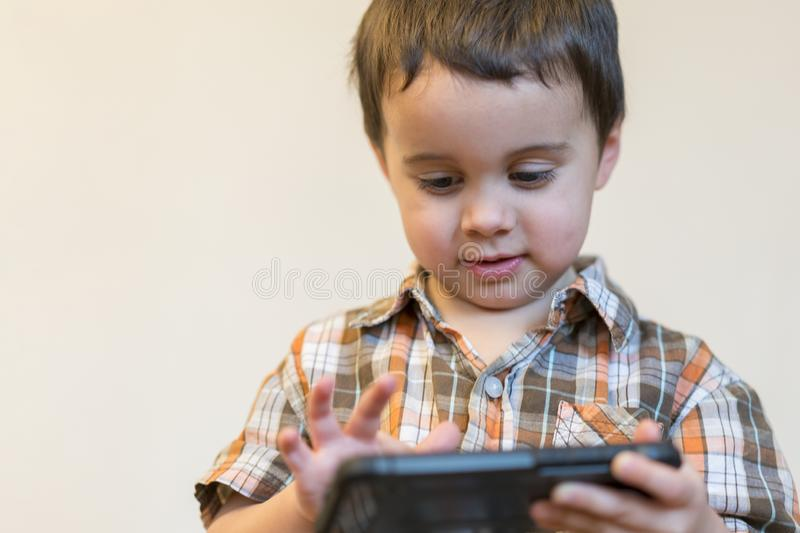 Portrait of a smiling little boy holding mobile phone isolated over light background. cute kid playing games on smartphone stock images