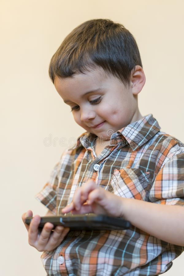 Portrait of a smiling little boy holding mobile phone isolated over light background. cute kid playing games on smartphone. stock photo