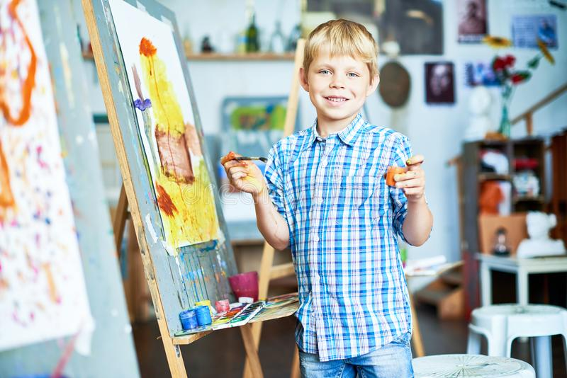 Happy Little Boy Enjoying Art Class. Portrait of smiling little boy painting on easel in art studio and posing, looking at camera, holding brush and paint, copy stock photography