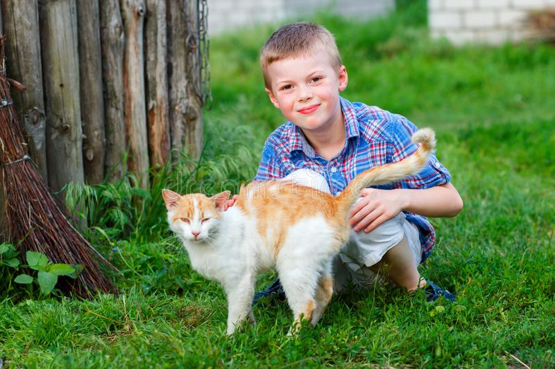 Portrait of a smiling little boy in a plaid shirt with a red cat, the boy stroked the cat, the cat arched his back and closed his royalty free stock photos