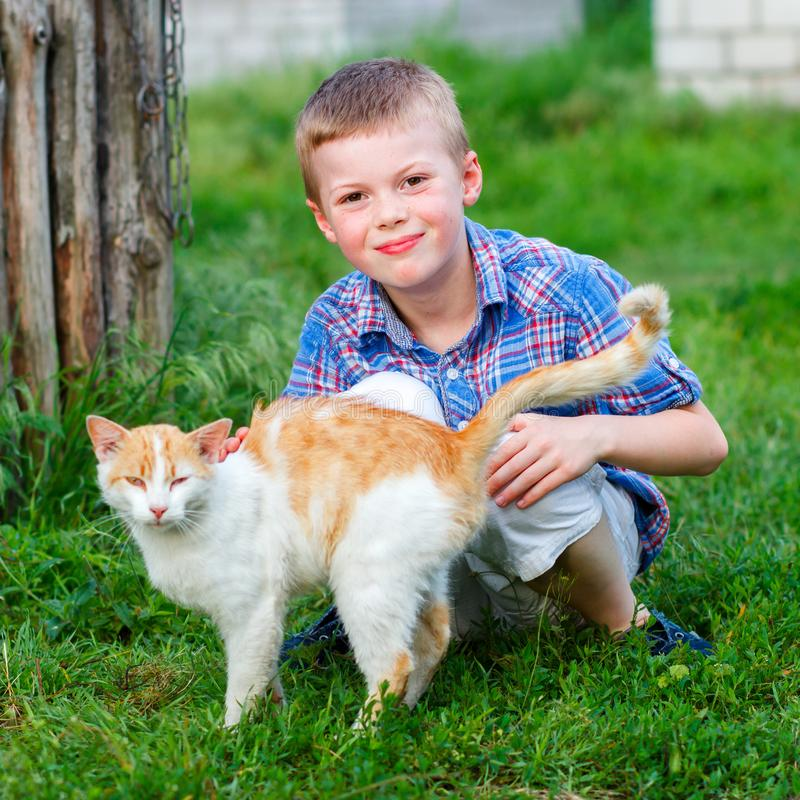 Portrait of a smiling little boy in a plaid shirt with a red cat stock image
