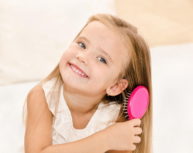 Portrait of smiling little girl brushing her hair royalty free stock images