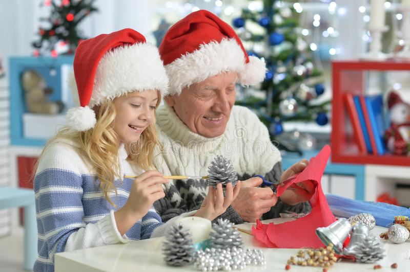 Girl with grandfather preparing for Christmas royalty free stock images