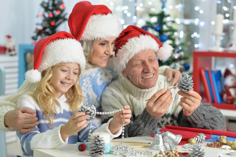 Girl with grandparents preparing for Christmas stock image