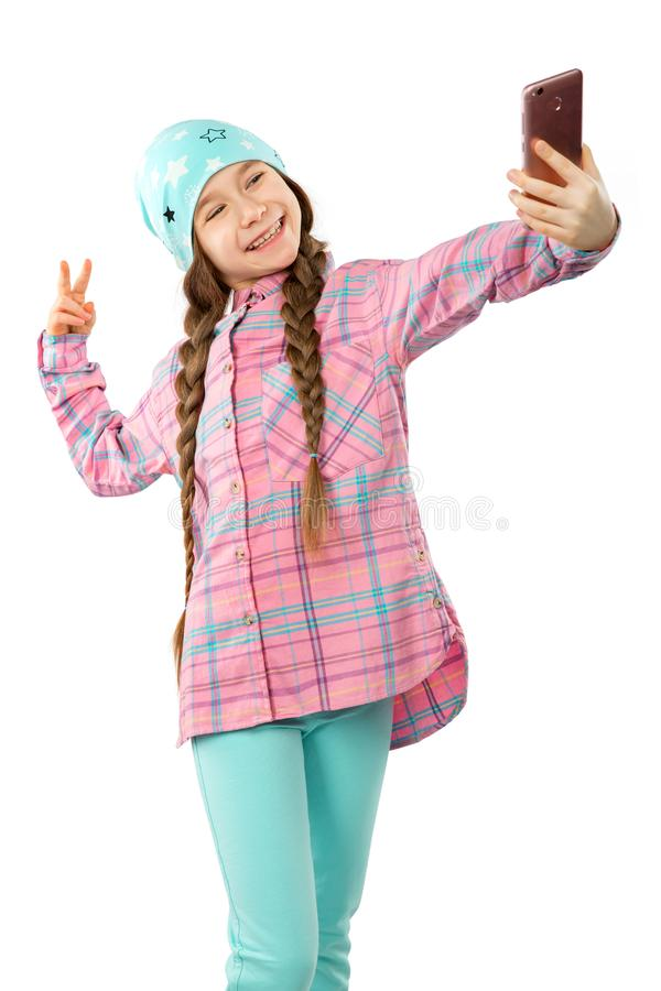 Portrait of a smiling little girl holding mobile phone and making selfie isolated on white background stock photos