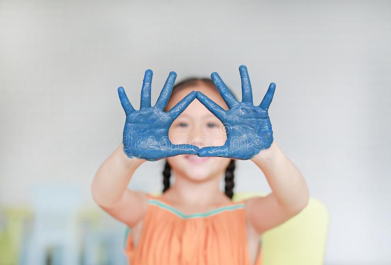 Portrait of smiling little girl looking through her blue hands painted in kids room. Focus at baby hands royalty free stock photography