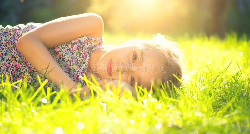 Portrait of a smiling little girl lying on green grass. Cute six years old child enjoying nature in summer park stock photography