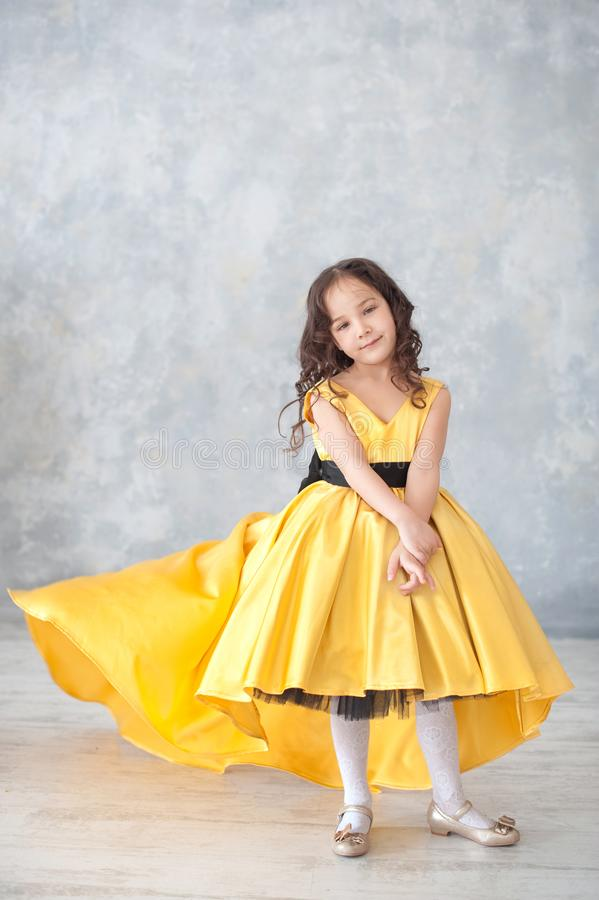 Portrait of smiling little girl in princess gold dress with butterflies royalty free stock images