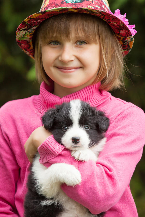 Portrait of a smiling little girl with a puppy Border Collie Outdoors stock image