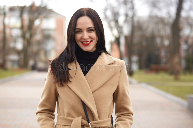 Portrait of smiling magnetic young lady standing in middle of city street, wearing in beige and black colours, urban background. stock images