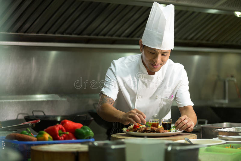 Portrait of a smiling male chef with cooked food standing in the kitchen. royalty free stock photo
