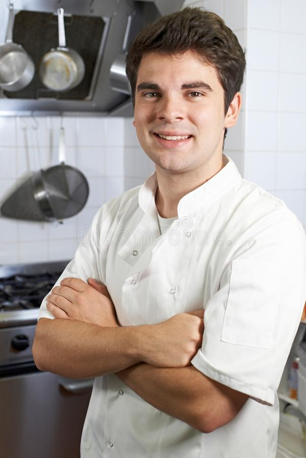 Portrait Of Male Chef Standing In Kitchen. Portrait Of Smiling Male Chef Standing In Kitchen royalty free stock photo