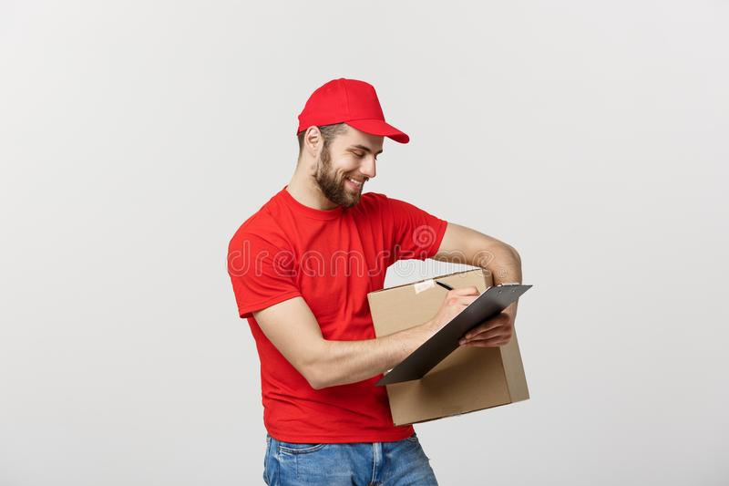 Portrait of smiling male delivery man writing on clipboard and holding box. Isolated over white background royalty free stock photo